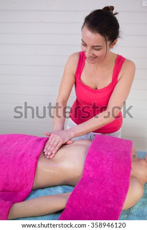 Beautiful young woman having a stomach massage by a female therapist - stock photo