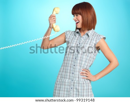 beautiful young woman, having a surprised face expression while talking on the telephone, on blue background - stock photo