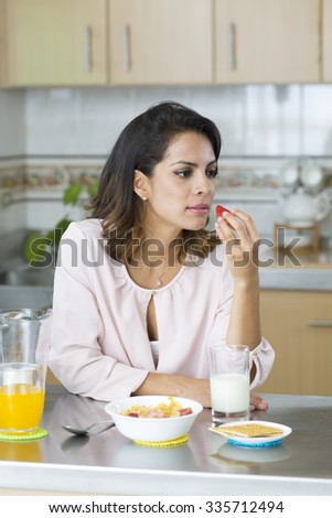 Beautiful young woman having breakfast, eating a strawberry - stock photo