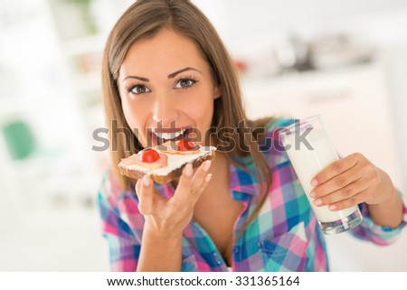Beautiful young woman having breakfast in the domestic kitchen. She is eating fresh sandwich and drinking milk. Looking at camera. - stock photo