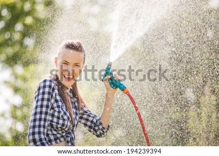 Beautiful young woman having fun in summer garden with garden hose splashing summer rain. soft backlight, motion - stock photo