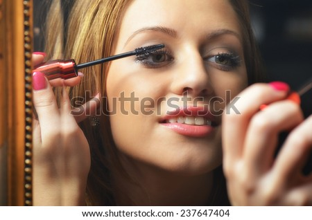 Beautiful young woman having fun while putting make up in front of the old mirror. - stock photo