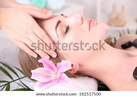 Beautiful young woman having  head and stone massage in spa salon
