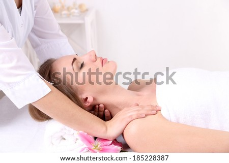 Beautiful young woman having head massage in spa salon