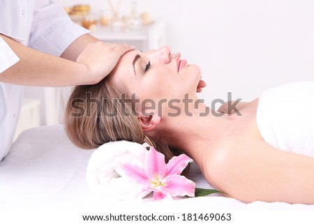 Beautiful young woman having head massage in spa salon, close-up