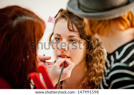 Beautiful young woman having her make up done by a make up artist in a studio - stock photo
