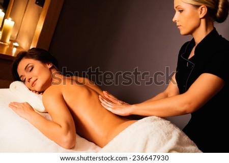 Beautiful young woman having massage in a spa salon - stock photo