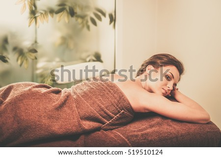 Beautiful young woman having massage in a spa salon.