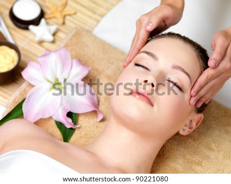 Beautiful young woman having spa massage of the head  in beauty salon - indoors - stock photo