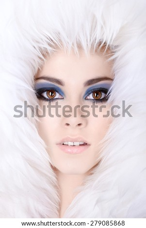 Beautiful young woman hiding in white fur. Winter portrait. - stock photo