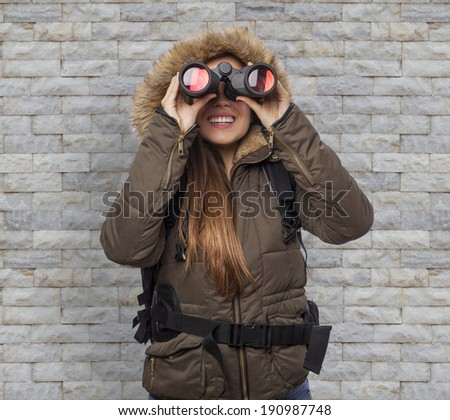 beautiful young woman hiker looking through binoculars - stock photo