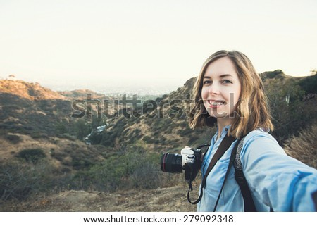 Beautiful young woman hiker taking selfie on the top of a mountain peak at Hollywood hills when hiking  - stock photo