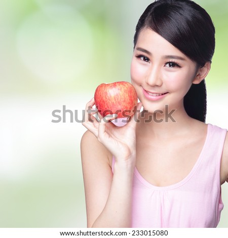 Beautiful young woman hold red apple with health teeth. Isolated over nature green background, asian beauty - stock photo