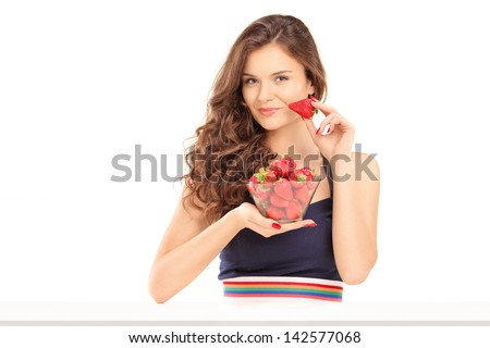 Beautiful young woman holding a bowl of strawberries, isolated on white background - stock photo