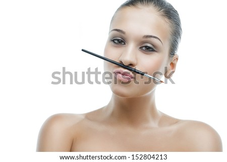 beautiful young woman holding a brush on the lips