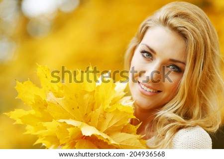 Beautiful young woman holding a bunch of autumn leaves - stock photo