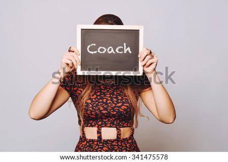 Beautiful young woman holding a chalkboard / blackboard saying coach. Caucasian young girl. - stock photo