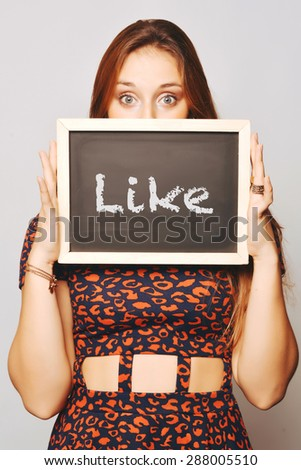 Beautiful young woman holding a chalkboard / blackboard saying like. Caucasian young girl. - stock photo