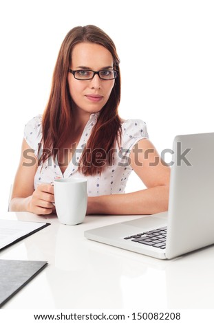 Beautiful young woman holding a cup of tea or coffee, in front a laptop, isolated on white