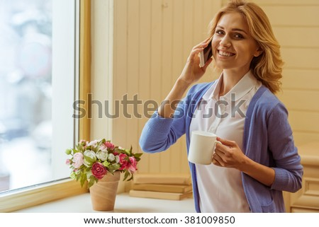 Beautiful young woman holding a cup, talking on the mobile phone, looking at camera and smiling while standing near the window - stock photo