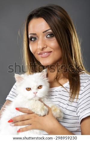 Beautiful young woman holding a cute white persian cat - stock photo