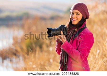 beautiful young woman holding a dslr camera outdoors in autumn - stock photo