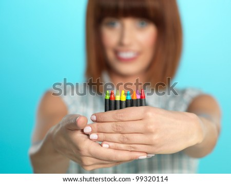 beautiful young woman, holding a few color crayons, smiling, on blue background