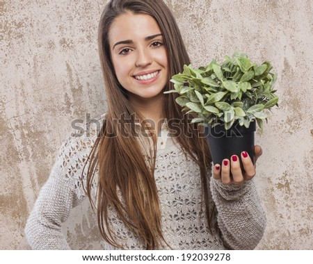 beautiful young woman holding a green plant - stock photo