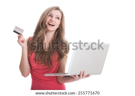 Beautiful young woman holding a laptop and credit or debit card and smiling while looking up thinking - stock photo