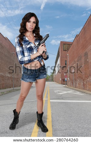Beautiful young woman holding a loaded handgun - stock photo