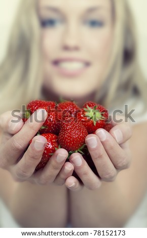 Beautiful young woman holding a lot of fresh strawberries