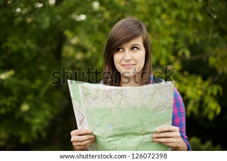 Beautiful young woman holding a map - stock photo