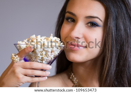 Beautiful young woman holding a martini glass filled with popcorn.