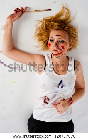 Beautiful young woman holding a paintbrushes at white background