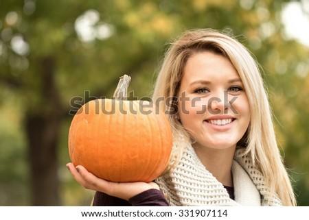 Beautiful young woman holding a pumpkin. - stock photo