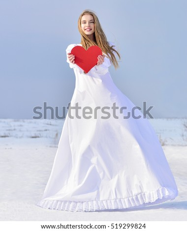 Beautiful young woman holding a red heart in the hands. Winter time.