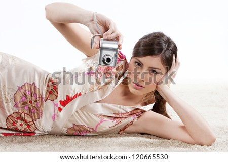 Beautiful young woman holding a silver modern digital photographic photo camera while laying down on a luxury carpet against a white background. - stock photo