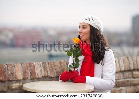 Beautiful young woman holding a single rose - stock photo