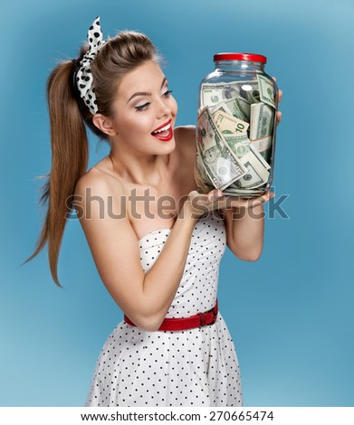 Beautiful young woman holding a transparent jar full of american dollars and happy smiling. Shopping concept - stock photo