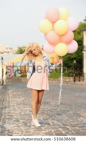 Beautiful young woman holding air balloons on street