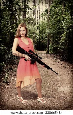 Beautiful young woman holding an automatic assault rifle - stock photo