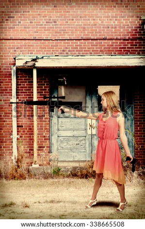 Beautiful young woman holding an automatic assault rifle and pistol - stock photo