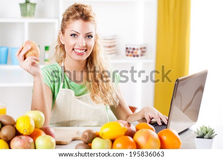 Beautiful young woman holding apple and reading recipe on laptop in kitchen. Looking at camera.