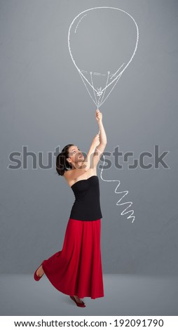 Beautiful young woman holding balloon drawing - stock photo