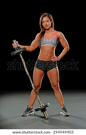 Beautiful young woman holding barbell over dark background