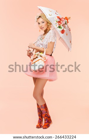 Beautiful young woman holding basket of flowers and umbrella over peachy background