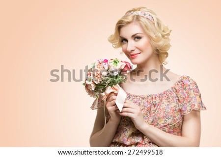 Beautiful young woman holding blooming bouquet of flowers in paste colors. - stock photo