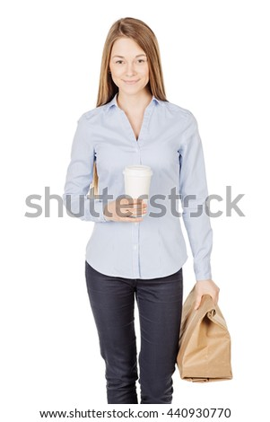 Beautiful young woman holding brown paper bag and hot drink in disposable paper cup