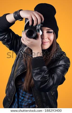 beautiful young woman holding camera on orange background - stock photo