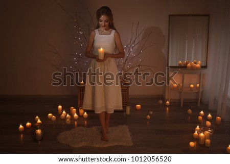 Beautiful young woman holding candle in dark room